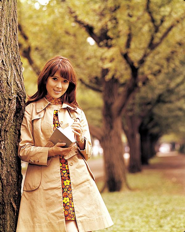トレンチコートを着て木のそばに立っているいしだあゆみの画像